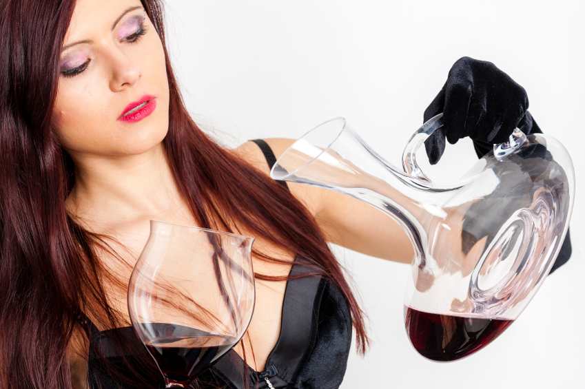 portrait of young woman with a glass of red wine and carafe